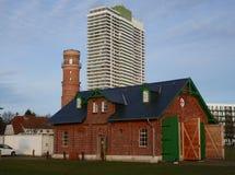 Nostalgi och modernitet, gammal fyr, gammal boatshouse och ett modernt hotell i en skyskrapa arkivbilder