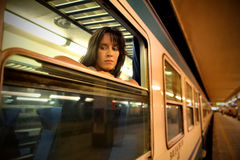 Nostalgia. Sad woman leaning against the window of a train Stock Photos