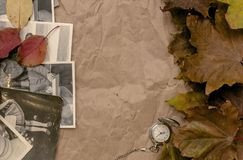 Nostalgia concept. Memoirs. Retro vintage background with copy space. Old vintage photos of peoples with no faces, pocket watch and autumn foliage on crumpled Stock Photos