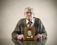 Nostalgia of the past. Senior man holding a photo of a child Stock Image