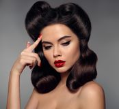 Nostalgia. Pin up girl with red lips makeup and retro curls hair. Style. Retro woman looking to the e holds a finger near the head. Expressive facial Stock Photography