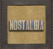 Nostalgia word framed. Nostalgia word assembled from vintage wooden letterpress inside stitched leather frame stock photo