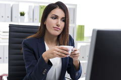 Nostalgic businesswoman with a cup of coffee in an office Stock Images