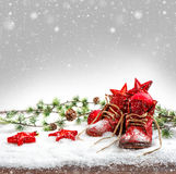 Nostalgic christmas decoration with antique baby shoes. Retro style picture with falling snow effect royalty free stock photos