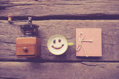 Nostalgic coffee grinder happy coffee cup. And handmade note book on wooden background Royalty Free Stock Photography