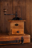 Nostalgic coffee grinder on old stool. And textured wood background Royalty Free Stock Photos