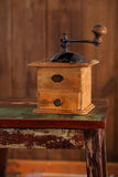 Nostalgic coffee grinder on old stool. And textured wood background Royalty Free Stock Photo