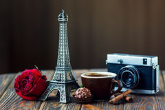 Nostalgic holidays background. Love Paris! Rose, vintage camera, Eiffel tower, coffee cup, chocolate and cinnamon sticks on wooden background. St Valentine's Day Royalty Free Stock Images