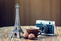 Nostalgic holidays background. Love Paris! Rose, vintage camera, Eiffel tower, coffee cup and chocolate on wooden background. St Valentine's Day concept Stock Photo