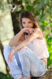 Nostalgic moments of a beautiful girl as she rests on a tree trunk. Woman wearing white short shirt and jean pants, sitting on a tree trunk , looking at the Royalty Free Stock Photography