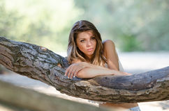 Nostalgic moments of a beautiful girl as she rests on a tree trunk Royalty Free Stock Photos