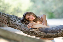 Nostalgic moments of a beautiful girl as she rests on a tree trunk Stock Photography
