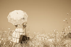 Nostalgic old photo in sepia color. Girl with her umbrella walki. Old photo in sepia color. Girl with her umbrella walking alone and searching her way Stock Photos