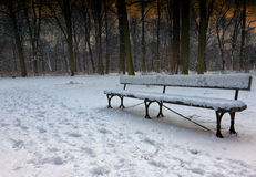 Nostalgic photo of snow-covered bench in the park in the winter, Royalty Free Stock Photo