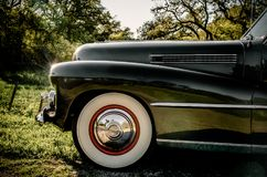 Nostalgic photograph of vintage car on a Texas country road. Side quarter section of 1941 Cadillac with large whitewall tires, sweeping fender, and long hood Stock Photos