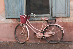 Nostalgic pink bike against house facade. Aged nostalgic pink bicycle, leaning against house wall and window stock images