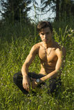 Nostalgic shirtless young man in a park as he kneels in green grass. Looking at camera stock images