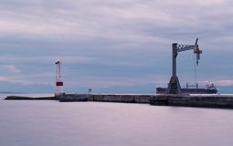 Nostalgic Thessaloniki`s port entrance breakwaters lighthouse. Port entrance breakwaters lighthouse and a small crane to lift objects royalty free stock images