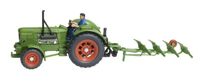 Nostalgic toy tractor with plowshare Stock Photos