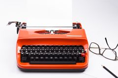 Nostalgic typewriter with pencil and glasses on white. Image shows a nostalgic typewriter with pencil and glasses isolated on white royalty free stock images