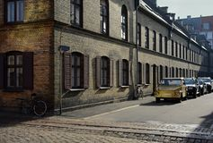 Nostalgic view of stoped time in Copenhagen street. Old yellow car in the street and broken bicycle near the old brick house on sunny day Royalty Free Stock Photography