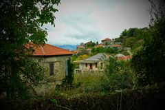 Nostalgic Vignette, Empty Greek Houses, Greece. Abandoned and empty Greek mountain village houses on a sombre and gloomy cloudy day.A nostalgic 1960`s vibe of a stock image