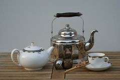 Closeup of an old water kettle with teapot, teacup, tea infuser and candy royalty free stock photography