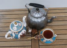 Topview of an old water kettle with teapot, teacup, tea infuser and candy stock photo