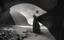 Nostalgic woman. Young woman walking under arch rock formation near Atlantic in Morocco stock images