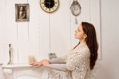 Nostalgic woman looking at an old family portrait. Nostalgic young woman in a stylish shawl standing with her hands resting on a marble mantelpiece looking at an stock images