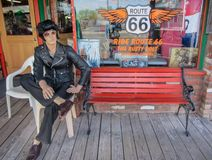 Nostalgicznego sklep z postacią Elvis Presley obsiadanie na ławce na trasie 66 arizonan USA Wiosna 2015 zdjęcia stock