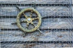 Nostalgicznego statku drewniana kierownica z siecią rybacką dołączał t Obrazy Royalty Free