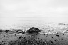Nostalgiczny morze Fala uderza w skale w centrum czarny white zdjęcie royalty free