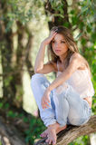 Nostalgische ogenblikken van een mooi meisje aangezien zij op een boomboomstam rust stock afbeelding