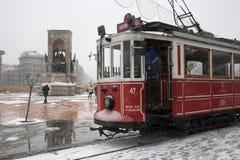 Nostalgisk spårvagn och Taksim monument av republiken på den snöig dagen Arkivbild