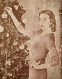 Nostalgy Christmas woman dressing Xmas tree. Stock Images