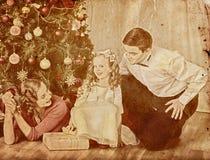 Nostalgy julfamilj med julgranen för barnflickadressing Arkivfoton