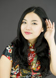 Nosy Asian young woman trying to listen carefully  on white background Stock Photo