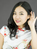 Nosy Asian young woman trying to listen carefully  on white background Stock Photos