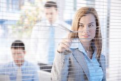 Nosy businesswoman peeping through blind smiling Stock Photos