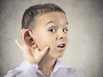 Nosy little boy, man listening carefully to someone's secrets. Closeup portrait, headshot boy, little man overhearing something, hand to big ear gesture, very stock photography