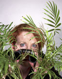 Nosy Neighbor. Woman looking through plant with binoculars Stock Photo