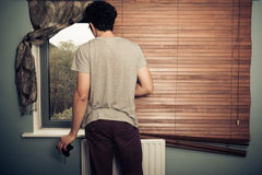 Nosy neighbour with binoculars. Standing by his window Stock Photography
