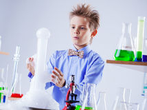 Nosy schoolboy watching reaction of experiment Royalty Free Stock Images