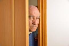 Nosy senior man. Cropped shot of senior man spying and entering through the door as concept of nosy man Stock Photo