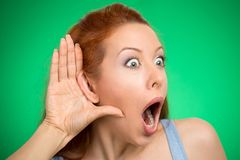 Nosy woman hand to ear gesture eavesdropping shocked Royalty Free Stock Image
