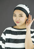 Nosy young Asian woman trying to listen carefully in prisoners uniform Royalty Free Stock Photos