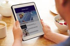 Notícia App de Person At Breakfast Looking At na tabuleta de Digitas foto de stock