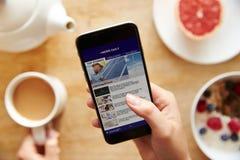 Notícia App de Person At Breakfast Looking At no telefone celular Foto de Stock Royalty Free