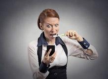 Notícia chocada da leitura da mulher nos dentes de escovadela do smartphone imagens de stock